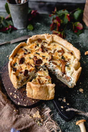 cooked appetizing pie with mushrooms on wooden table