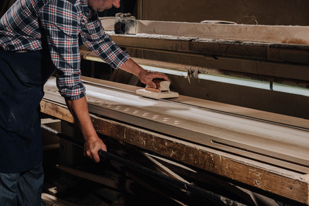 cropped shot of woodworker planing wood with hand plane at workshop