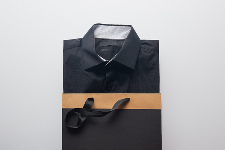 top view of new black shirt in shopping bag isolated on white Stock Photo