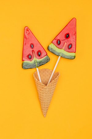 top view of tasty lollipops in shape of watermelon in waffle cone isolated on orange