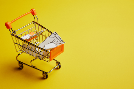 close up view of little shopping cart with clothes made of paper on yellow background Stock fotó