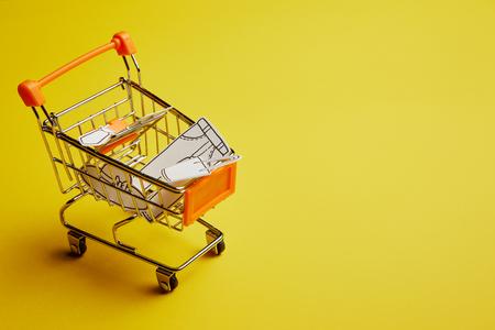 vista ravvicinata del piccolo carrello con vestiti di carta su sfondo giallo