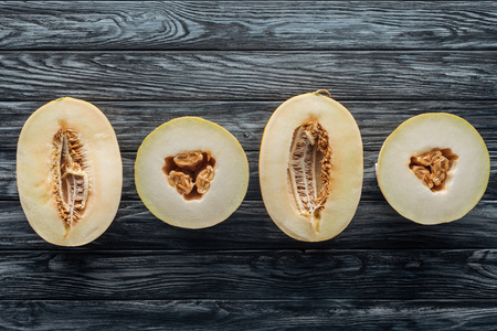 top view of halved ripe sweet melons on wooden surface Stock Photo