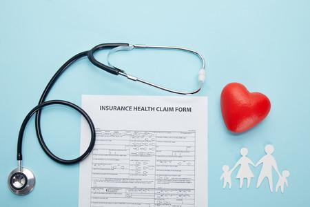 Draufsicht auf Versicherungsfallformular, Papierschnittfamilie, rotes Herzsymbol und Stethoskop auf Blau