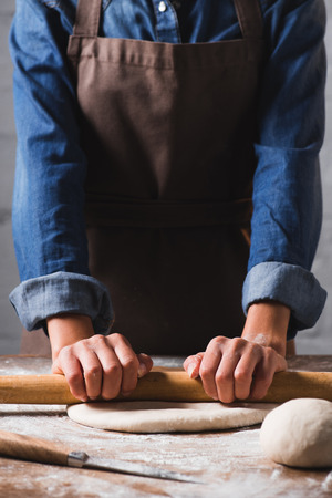 partial view of woman with rolling pin kneading dough for pizza