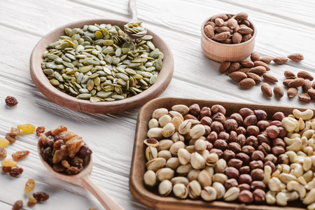 Assorted delicious nuts and raisins in wooden plates and spoon
