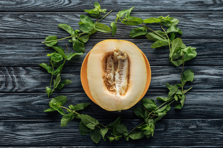 top view of fresh ripe sweet melon and fresh mint on wooden surface Stock Photo