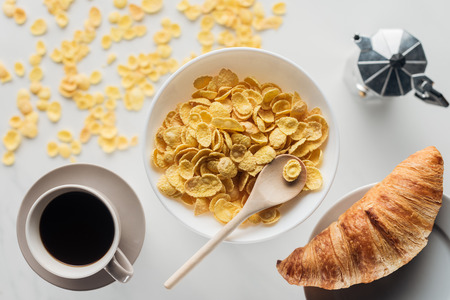 top view of bowl of corn flakes breakfast with cup of coffee and croissant on white