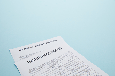 close-up view of insurance form and insurance health claim form isolated on blue