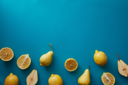 top view of pears and lemons on blue surface