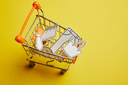 close up view of little shopping cart with clothes made of paper on yellow background Фото со стока