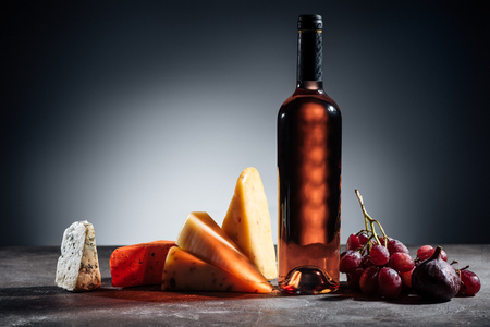bottle of red wine, different types of cheeses and grapes on grey