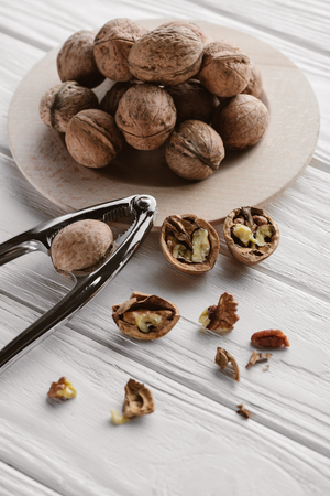 delicious walnuts with metal nutcracker on wooden table
