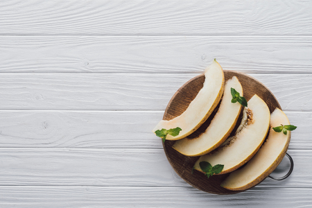 top view of sweet ripe sliced melon with mint in round wooden board on table