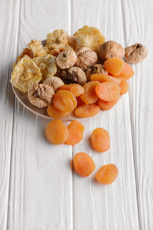 Variety of dried fruits on white plate on wooden surface
