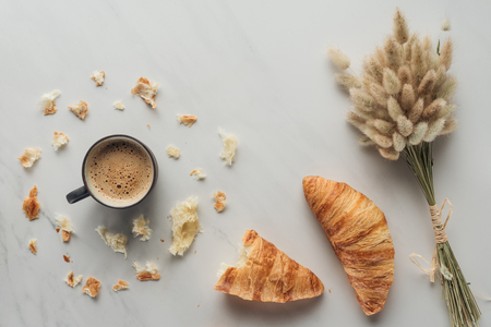 top view of cup of coffee with croissants and bouquet of bunnytail ears on white marble