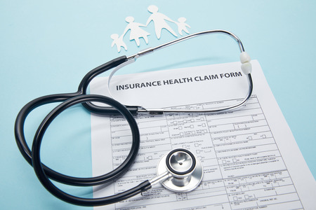 close-up view of insurance health claim form, paper cut family and stethoscope on blue