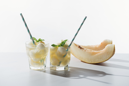 slices of sweet honeydew melon and refreshing beverage with melon and mint in glasses on white