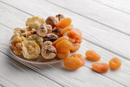 Gemischte getrocknete Früchte auf weißem Teller auf Holztisch Standard-Bild