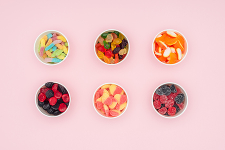 top view of paper cups with jelly candies isolated on pink