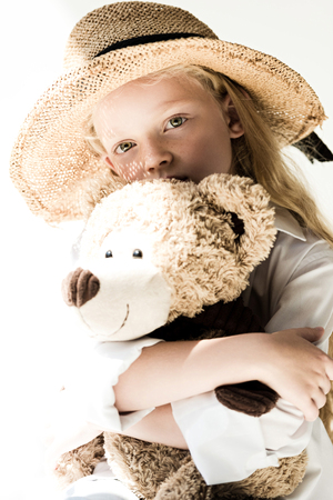 beautiful child in straw hat hugging teddy bear and looking at camera on white Stock Photo