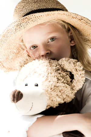 adorable child in wicker hat holding teddy bear and looking at camera on white