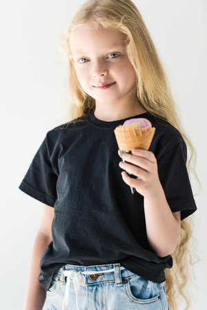 adorable child in black t-shirt eating ice cream and smiling at camera isolated on white Zdjęcie Seryjne