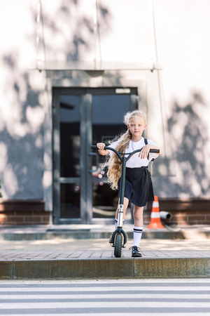 adorable schoolgirl riding scooter and looking at camera on street