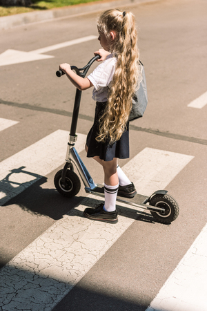 high angle view of adorable little schoolgirl with long curly hair riding scooter on street 免版税图像