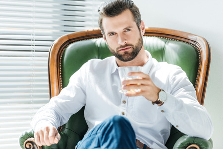 handsome elegant man holding glass of whiskey and sitting in green armchair