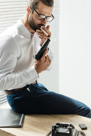 handsome fashionable businessman smoking cigar with gun