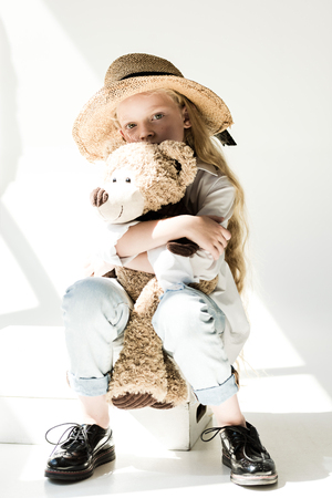 full length view of adorable child in straw hat hugging teddy bear and looking at camera on white