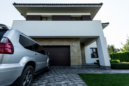 facade of new modern house with car on parking Stock Photo