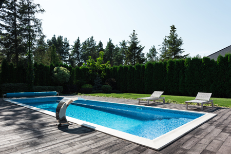 view of poolside with sunbeds and green lawn