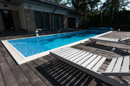 view of house exterior, swimming pool with sunbeds