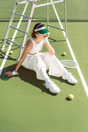 young woman in fashionable white clothing and cap sitting on tennis court with racket and balls