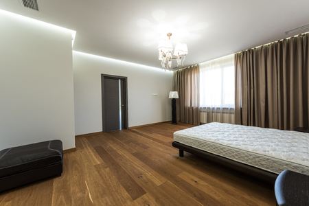 interior of modern bedroom with big window and mattress on bed
