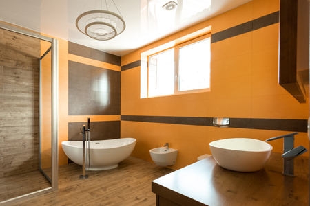 interior of bathroom in orange and white colors with bathtube, sink and bidet