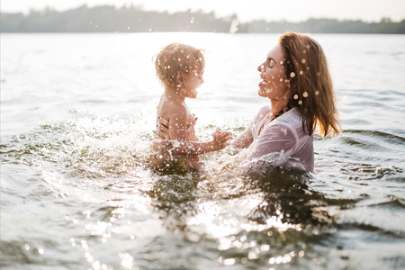 side view of happy mother and daughter swimming in river Stockfoto