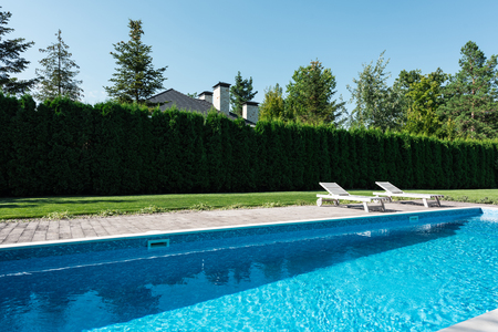 view of swimming pool with sunbeds and green fence