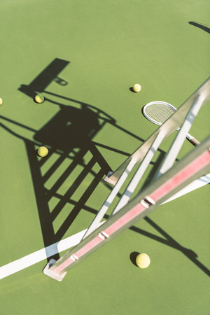 close up view of metal referee chair , tennis racket and balls on green tennis court Reklamní fotografie