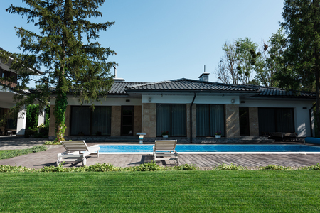 view of modern house, poolside with sunbeds and green lawn
