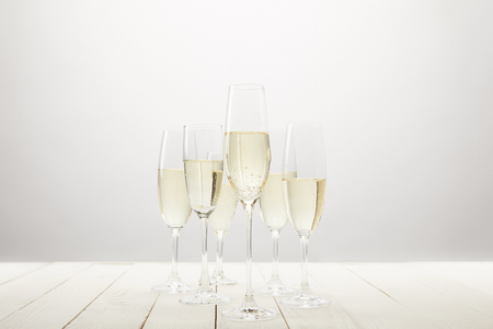 closeup view of champagne glasses on white wooden table