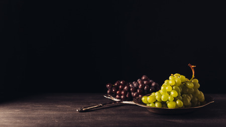 fresh ripe red and white grapes on plates and vintage knife on wooden table on black