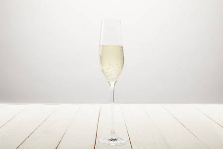 closeup view of champagne glass with bubbles on white wooden table Stock Photo