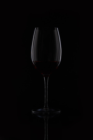 closeup shot of glass with red wine isolated on black background Stock Photo