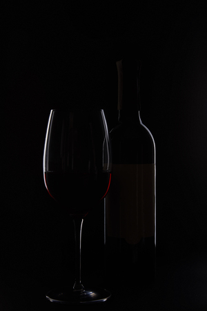 closeup shot of bottle and glass with red wine isolated on black background Stock Photo - 107187639