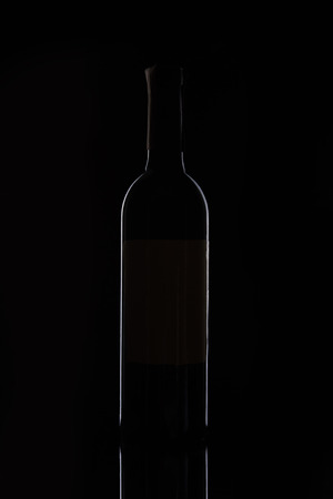 closeup view of bottle with red wine isolated on black background Stock Photo