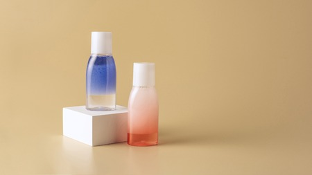 close up view of face wash in bottles on white cube on beige backdrop Stock Photo