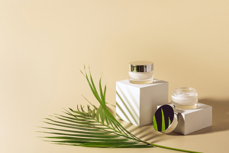 close up view of green palm leaf, facial and body creams in glass jars on white cubes on beige background